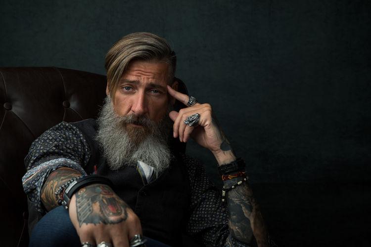 Portrait Of Bearded Man Sitting Against Black Background