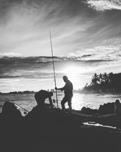 Silhouette men fishing at beach against sky