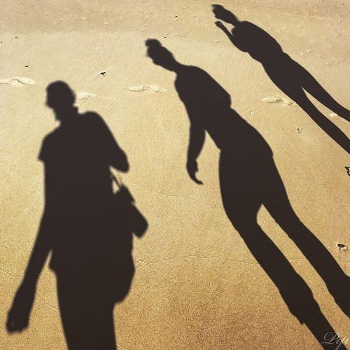 Shadow of women walking at beach