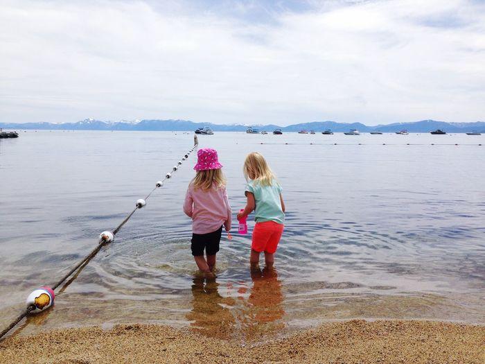 Rear View Of Siblings Standing At Lake Against Sky