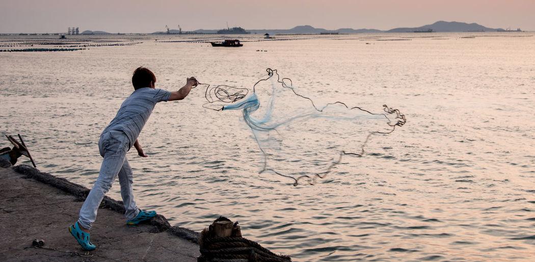 Fisherman throwing fishing net in sea during sunset