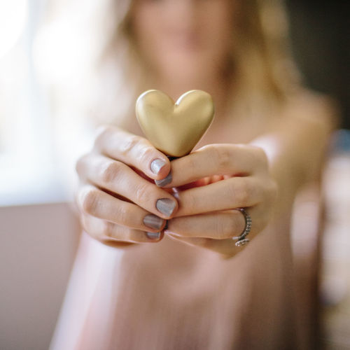 woman holding a golden heart Human Hand Holding Valentines, Sweetheart, Love, Heart, Golden, Bokeh, Hand, Focus On Foreground Hand Close-up Indoors  Adult Ring One Person Heart Shape Emotion Midsection Women Jewelry Front View Human Body Part Real People Nail Human Finger Finger