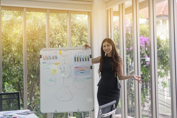 Businesswoman presenting works in the meeting room. BoardRoom Business Meeting Office Working Young Adult Businesswoman Casual Clothing Checklist Clipboard Colleagues Female Finance Hairstyle Job Looking Manager person Portrait Recruitment Report Technology Women Young Adult