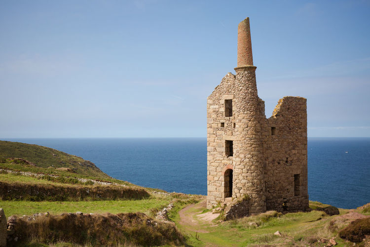 A derelict Cornish tin mine building at Botallack in Cornwall, UK which is associated with the Poldark TV series. Architecture Beauty In Nature Building Building Exterior Built Structure Cornwall Day Heritage History Horizon Horizon Over Water Land Mining Nature No People Old Outdoors Poldark Ruined Scenics - Nature Sea Sky The Past Tin Mine Tower