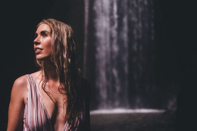 Woman looking away while standing against waterfall