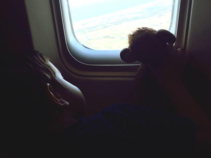 Boy with toy sitting by airplane window