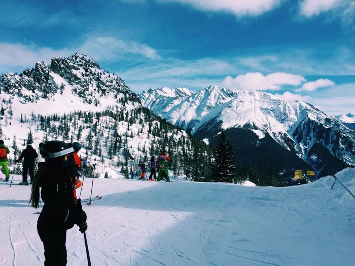 People skiing on snow covered field against mountains