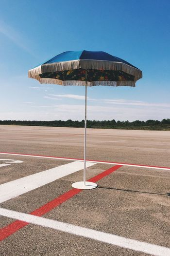 Parasol At Airport Runway Against Sky