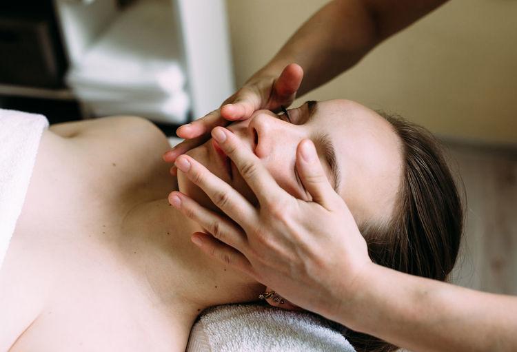 Cropped hand of massage therapist massaging woman face
