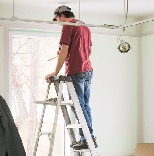 Full Length Of Man Standing On Ladder While Working At Home