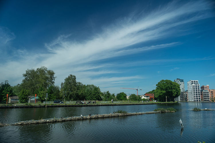 Scenic view of river against sky in city