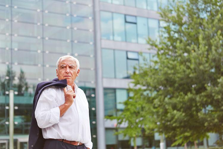 Thoughtful Senior Businessman Standing Against Modern Building