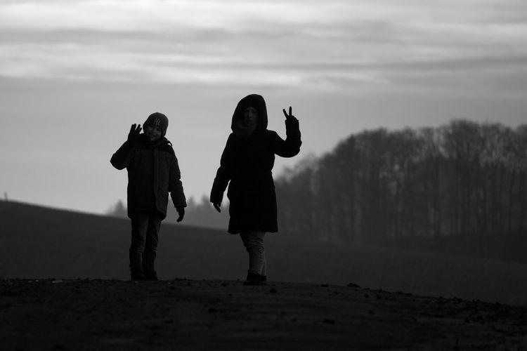 Full length of friends standing on land against sky