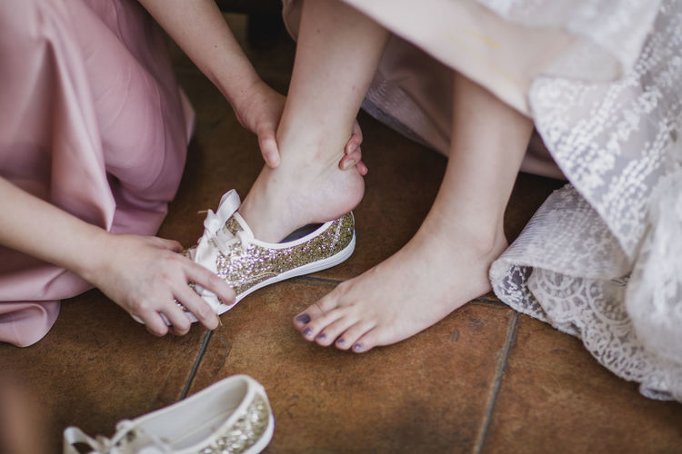 Woman assisting bride in wearing shoes on floor