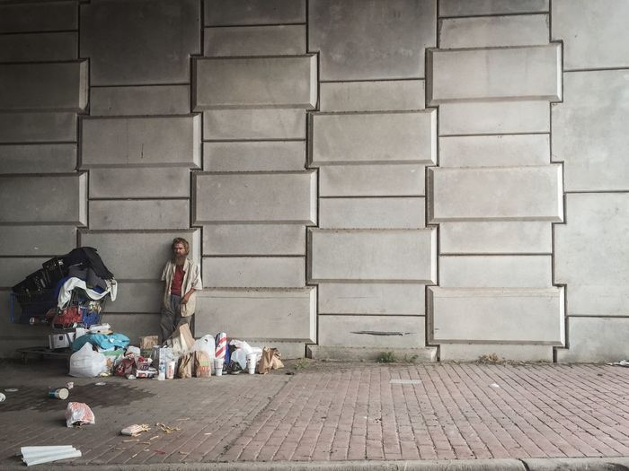 Homeless Man Standing By Shopping Cart And Bags Against Wall
