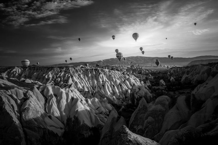 Panoramic shot of hot air balloons on rock formation against sky