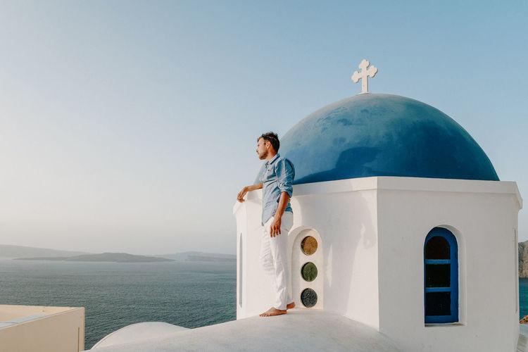 Man standing at chapel by sea at santorini