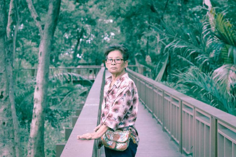 Portrait of smiling woman standing on footbridge