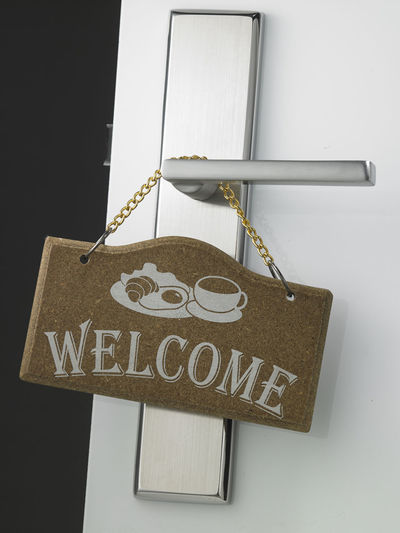 Close-Up Of Welcome Text Hanging On Door Handle