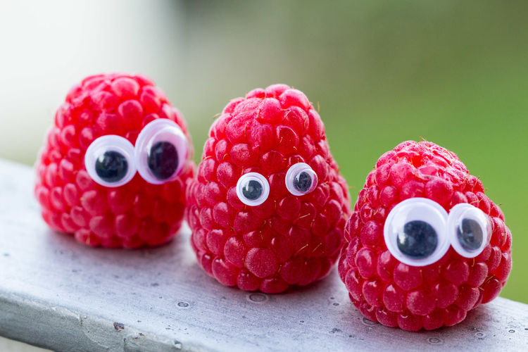 Close up of raspberries with googly eyes on wooden railing