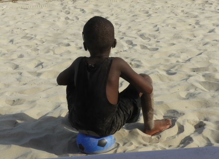 Rear view of boy sitting on ball at beach