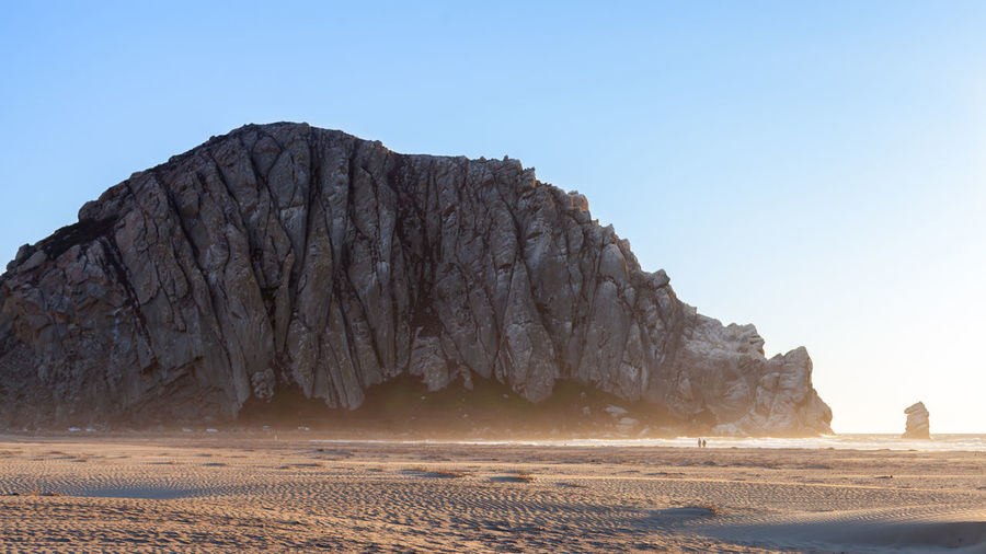 Rock Formations By Beach Against Clear Blue Sky