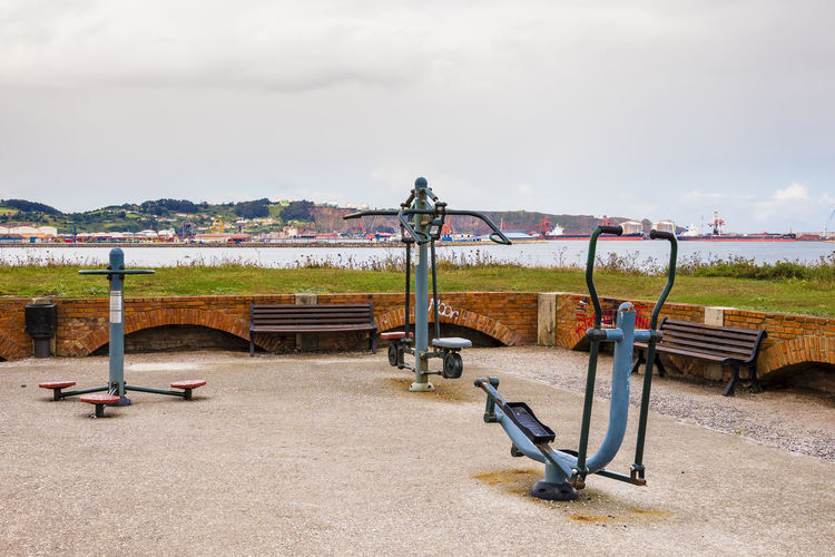 View of playground by lake against sky