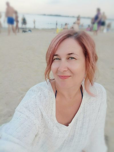 Portrait of smiling woman sitting at beach