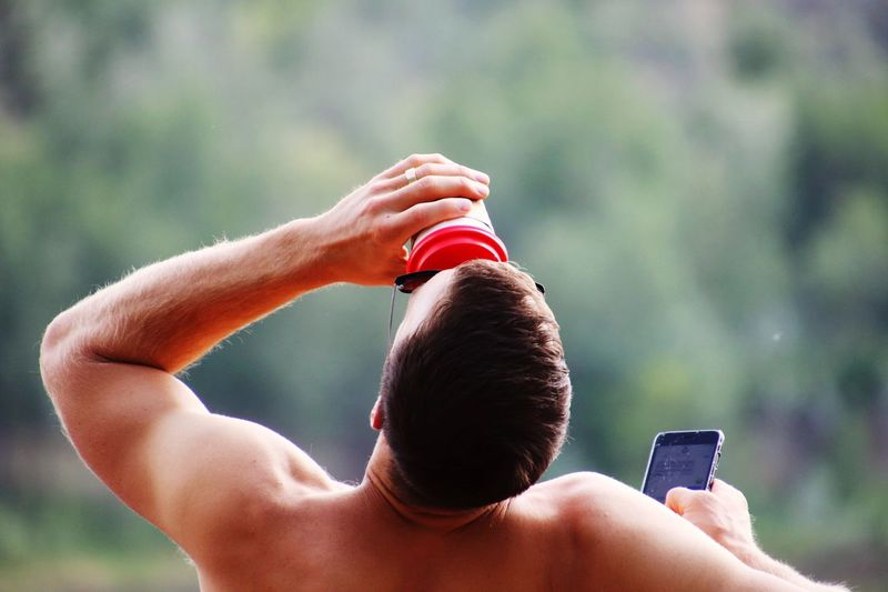 Rear view of shirtless man drinking while using mobile phone