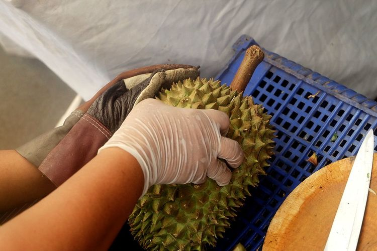 Cropped image of hands holding durian