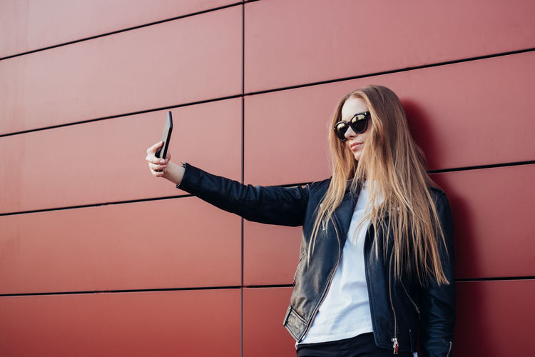 Woman Taking Selfie While Standing Against Red Wall