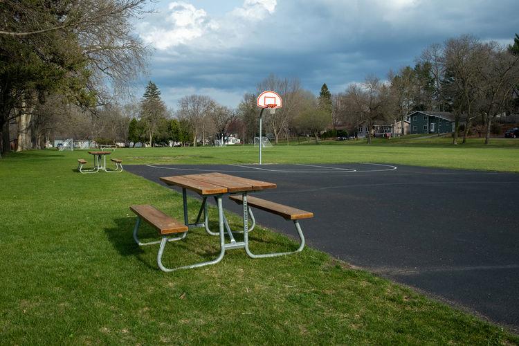 Empty bench in park against sky