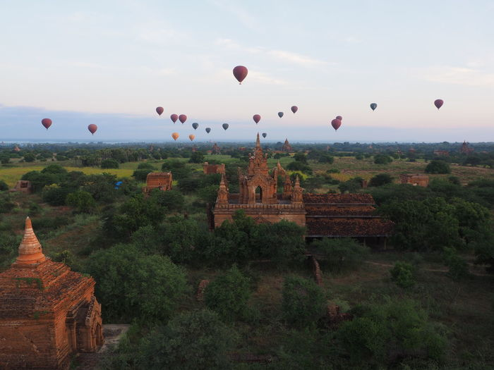 Hot Air Balloons Over Temple On Field At Bagan