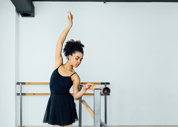 Young woman practicing ballet by railing in studio