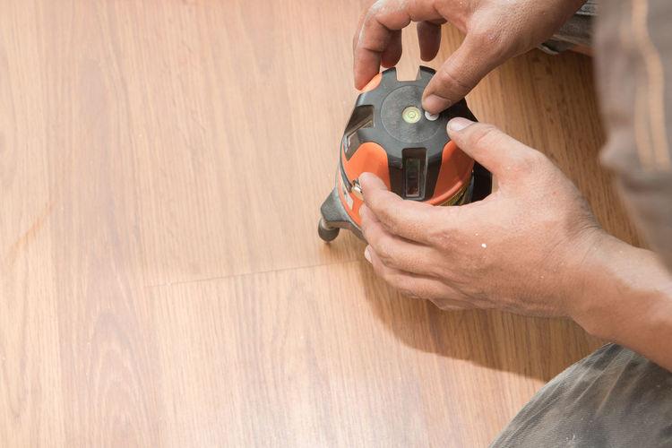 Cropped Image Of Carpenter Working On Hardwood Floor