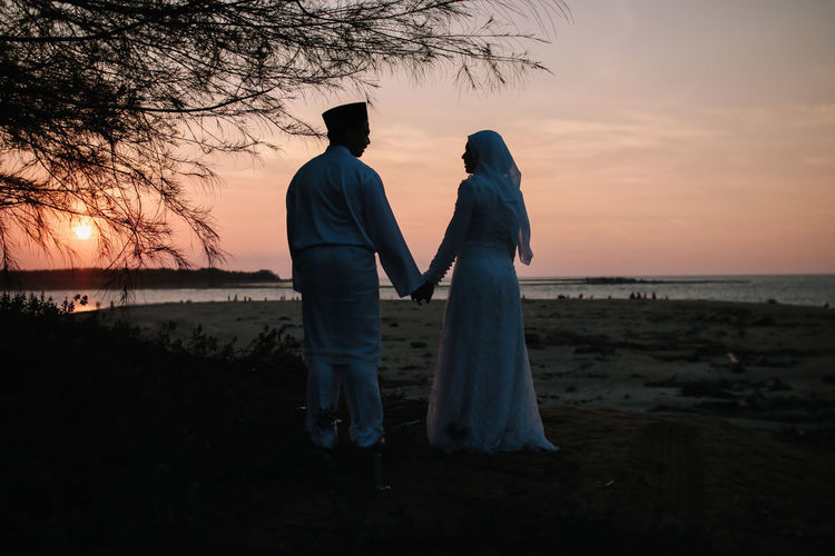 Young couple holding hands while standing at beach during sunset