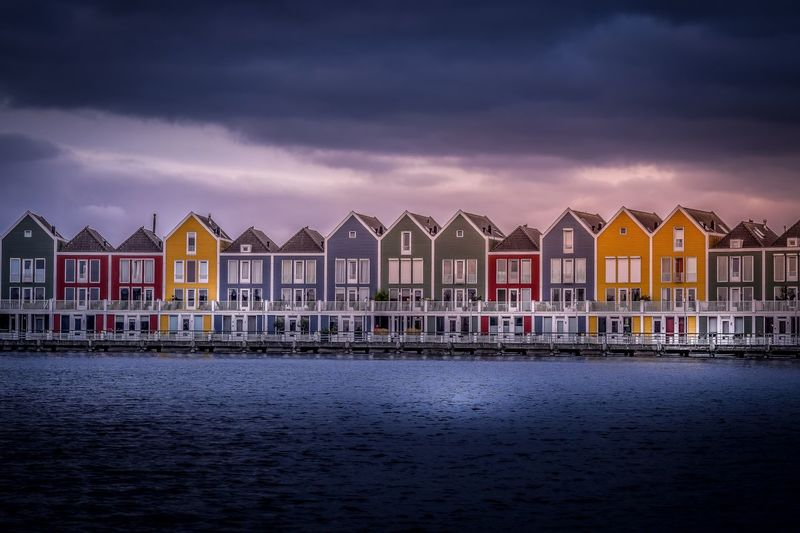 Houses by sea against sky during sunset
