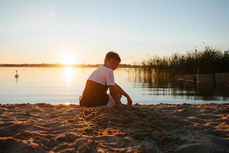 Boy sitting on beach against sky during sunset