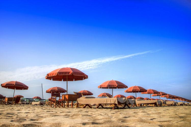 Parasols At Beach Against Blue Sky