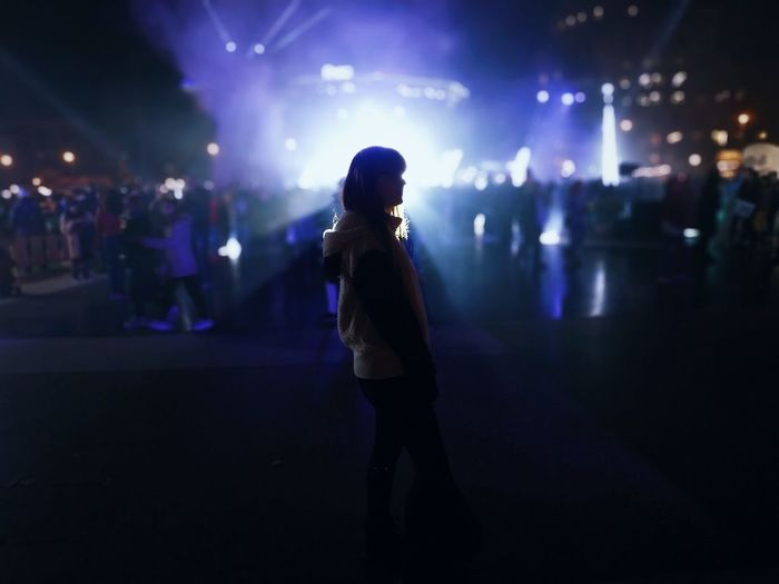Full length of woman standing in city at night
