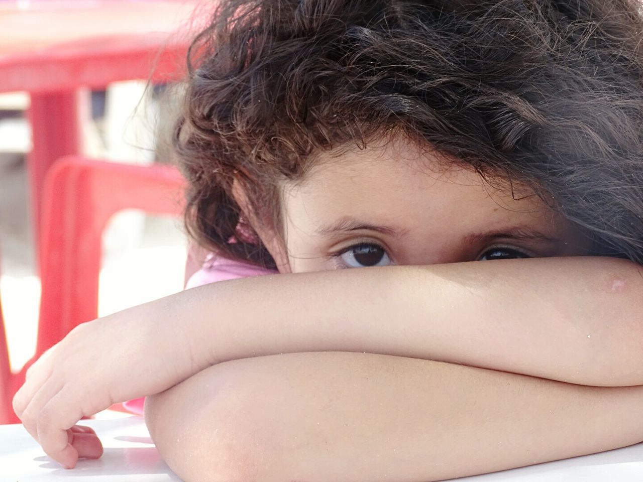 Portrait Of Girl Covering Face With Arms While Leaning On Table