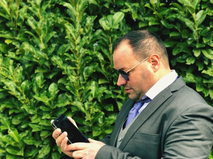 Businessman in sunglasses using mobile phone by plants