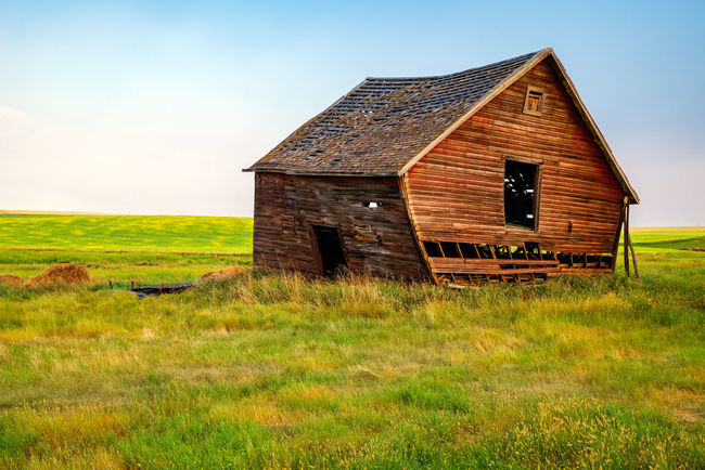 Abandoned Homestead - Leaning Barn Agricultural Building Architecture Building Building Exterior Built Structure Day Environment Field Grass Green Color House Land Landscape Nature No People Non-urban Scene Outdoors Plant Ruined Rural Scene Scenics - Nature Sky