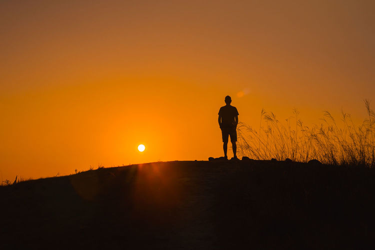 Adventure travel from silhouette man hiking and stand on top of the mountain in summer season