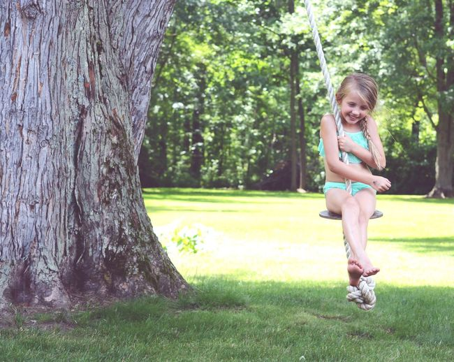 Childhood Swinging From A Tree Rope Swing Happiness Tree Smiling Child Outdoors Playing Tree Trunk Nature Happiness One Girl Only Nature Day EyeEm Selects EyeEmNewHere EyeEmNewHere The Week On EyeEm
