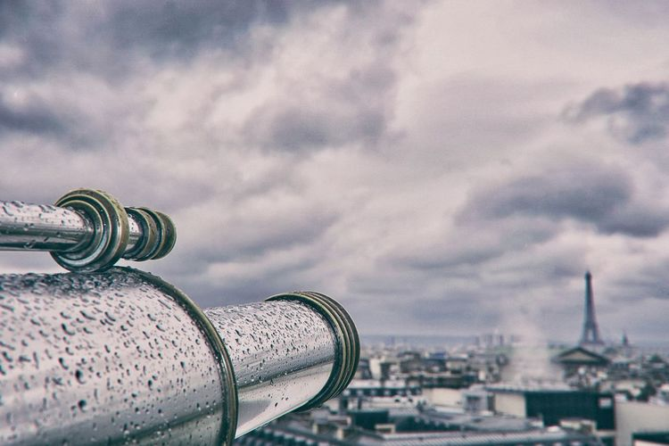 Close-up of cityscape against cloudy sky with telescope