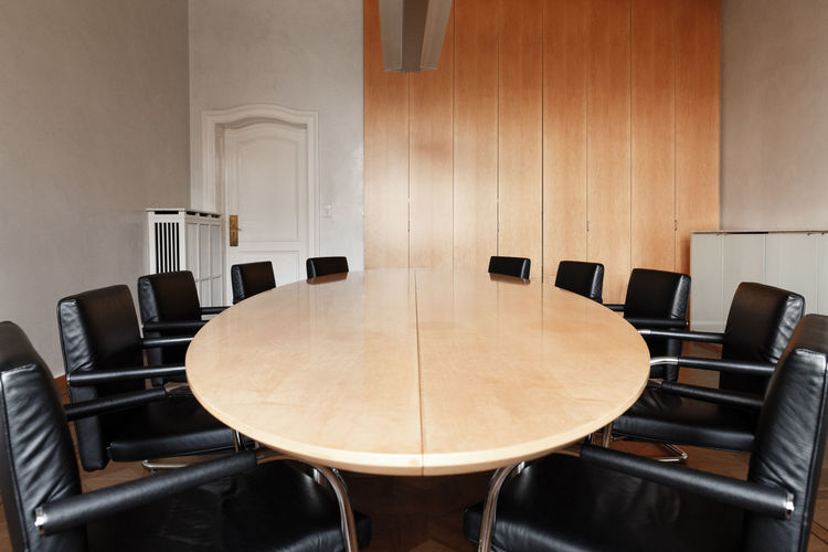 Empty chairs by conference table in office