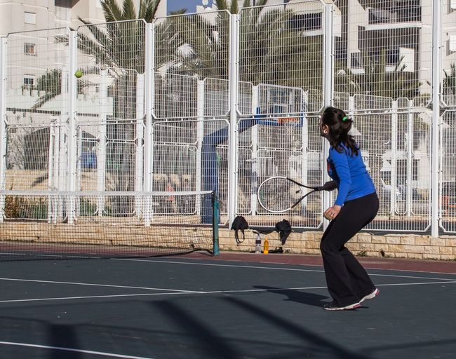Side View Woman Playing Tennis On Court During Sunny Day