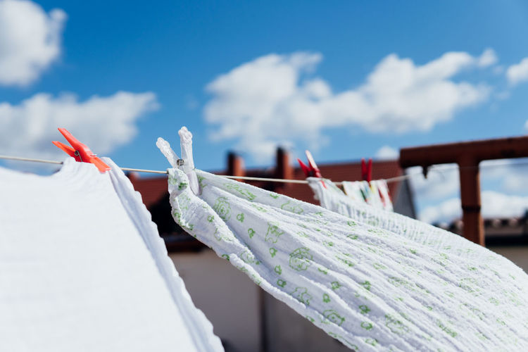 Close-up of clothes drying on rope against sky