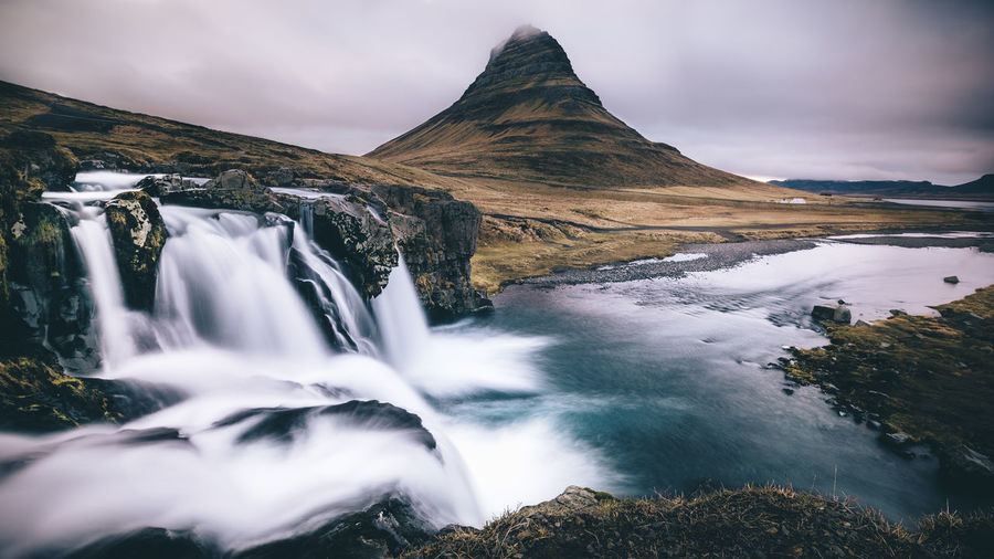 Kirkjufell Mountain And Waterfall Against Sky